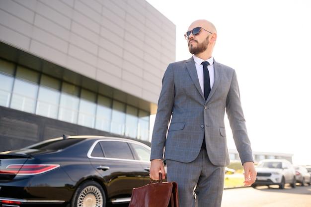 Ritratto di un uomo d'affari bello in occhiali da sole che stanno vicino all'automobile all'aperto davanti alla facciata moderna della costruzione