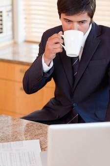 Ritratto di un uomo d'affari che beve caffè durante l'utilizzo di un computer portatile