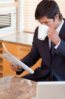 Ritratto di un uomo d'affari che beve caffè durante la lettura delle notizie