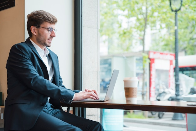 Ritratto di un uomo d'affari che utilizza computer portatile con la tazza di caffè asportabile sulla tavola in caffè