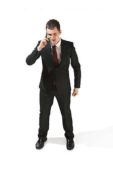 Ritratto di un uomo d'affari con la faccia molto seria e parlando al telefono
