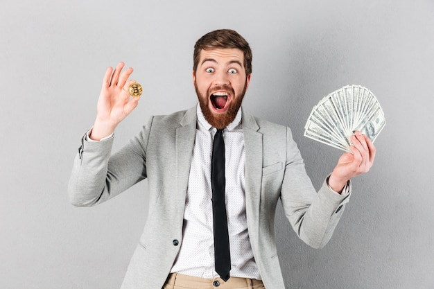 Ritratto di un uomo d'affari eccitato che mostra bitcoin