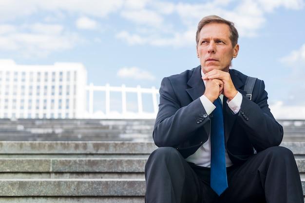 Ritratto di un uomo d'affari maturo che si siede sulla scala