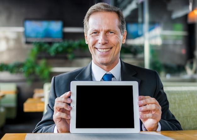 Ritratto di un uomo d'affari maturo felice che mostra compressa digitale