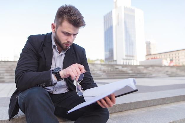 Ritratto di un uomo d'affari seduto sulla strada per le scale e la lettura di documenti nelle sue mani.