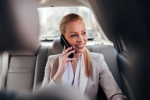 Ritratto di un uomo d'affari sorridente che parla sullo smartphone nell'automobile.
