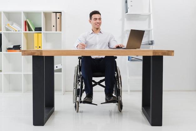 Ritratto di un uomo d'affari sorridente che si siede sulla sedia a rotelle con laptop sul posto di lavoro