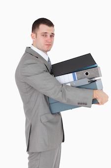 Ritratto di un uomo d'affari stressato in possesso di una pila di leganti