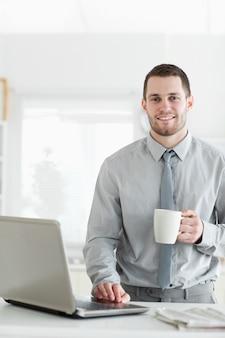 Ritratto di un uomo d'affari utilizzando un notebook mentre si beve il caffè