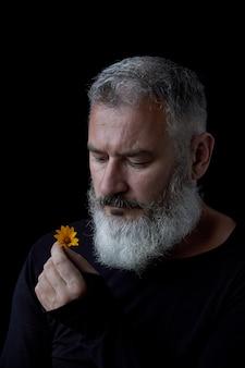 Ritratto di un uomo dai capelli grigio brutale con una barba che fiuta i fiori gialli su un fondo nero, fuoco selettivo