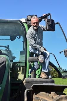 Ritratto di un uomo e un trattore dell'agricoltore