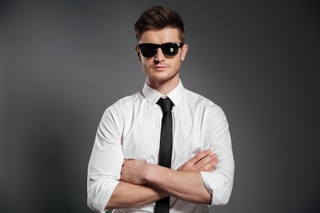 Ritratto di un uomo fiducioso in camicia e cravatta in piedi