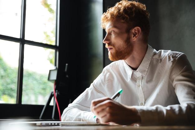 Ritratto di un uomo giovane rossa scrivendo su un quaderno