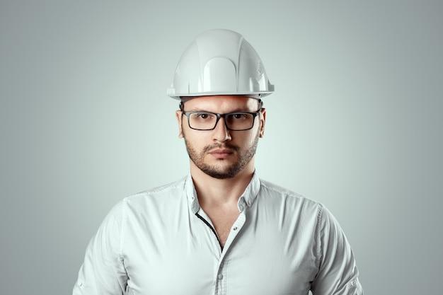 Ritratto di un uomo in un casco bianco costruzione. architettura concettuale, costruzione, ingegneria, progettazione, riparazione. copia spazio