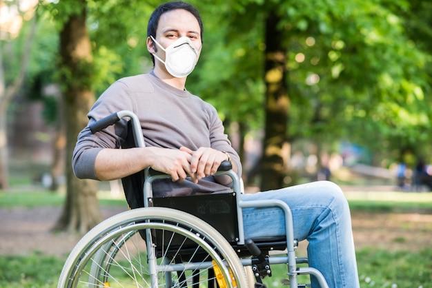 Ritratto di un uomo mascherato su una sedia a rotelle durante la pandemia di coronavirus