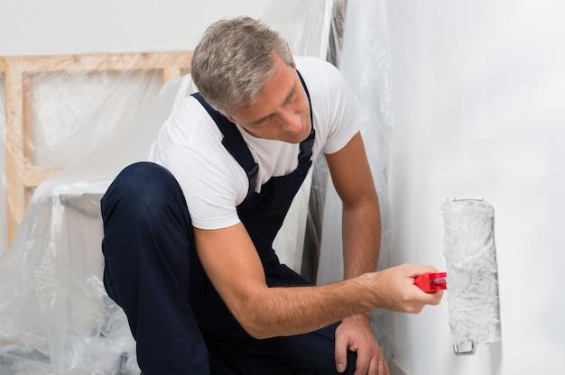 Ritratto di un uomo maturo sulla parete della pittura con il rullo