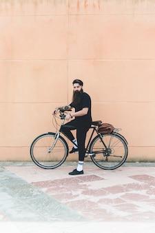 Ritratto di un uomo moderno in piedi con la sua bicicletta contro il muro