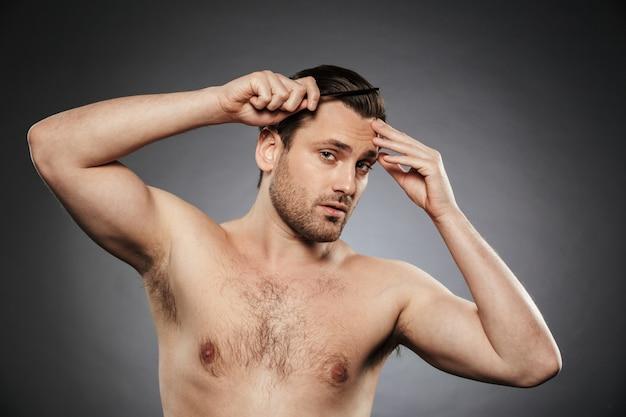 Ritratto di un uomo senza camicia bello che pettina i suoi capelli