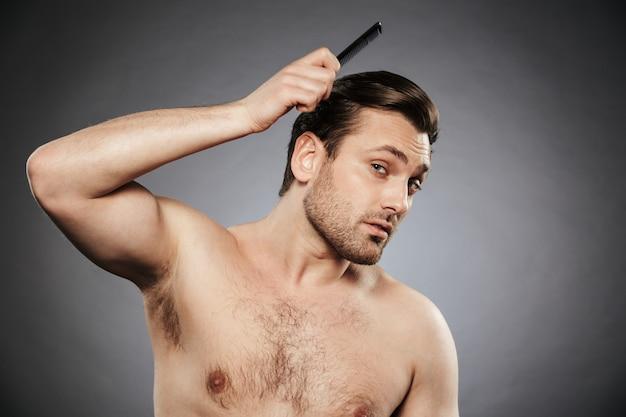 Ritratto di un uomo senza camicia concentrato che si pettina