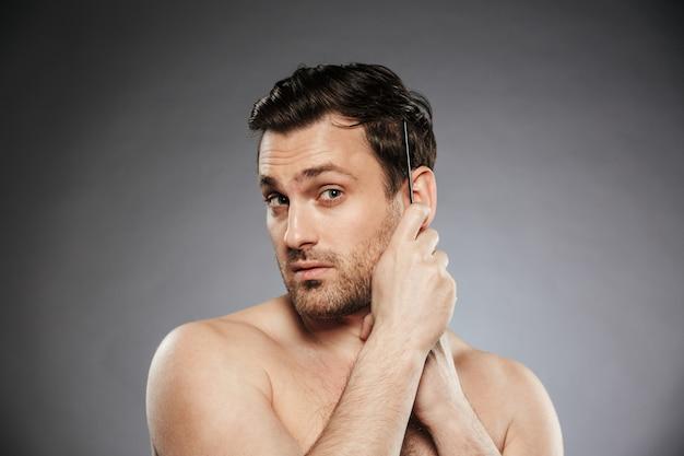 Ritratto di un uomo senza camicia sicuro che pettina i suoi capelli