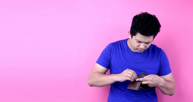 Ritratto di un uomo senza parole scioccato e sorpreso in asia, in possesso di un portafoglio vuoto su sfondo rosa in studio