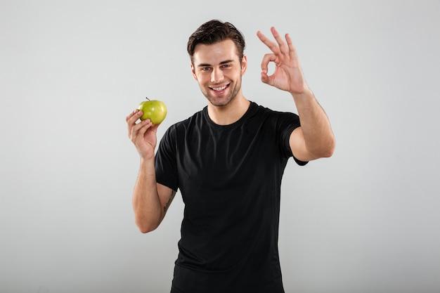 Ritratto di un uomo sorridente felice che tiene mela verde