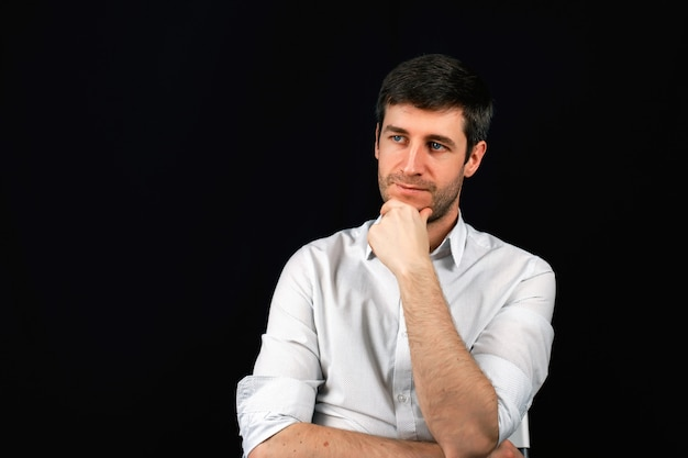 Ritratto di un uomo su uno sfondo nero. un uomo d'affari sta pianificando un lavoro.