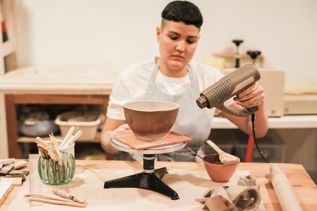 Ritratto di un vasaio femminile che asciuga la pittura con l'essiccatore nell'officina