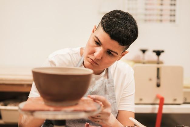 Ritratto di un vasaio femminile che lavora alla ciotola dell'argilla nell'officina
