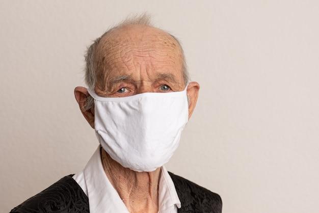 Ritratto di un vecchio, 80 anni, in maschera medica. un concetto del pericolo di coronavirus per gli anziani.