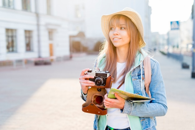 Ritratto di un viaggiatore femminile in città che tiene macchina fotografica d'epoca e mappa in mano guardando lontano