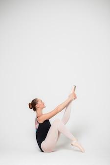 Ritratto di una ballerina su uno sfondo bianco, una giovane donna è seduta sul pavimento facendo stretching gambe.