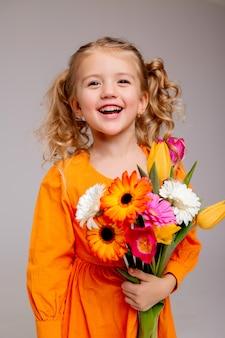 Ritratto di una bambina bionda con un mazzo di fiori primaverili su un muro chiaro