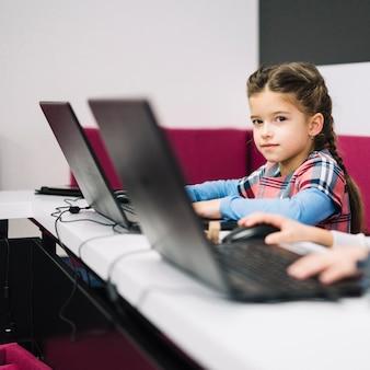 Ritratto di una bambina che guarda l'obbiettivo che si siede con il computer portatile in classe