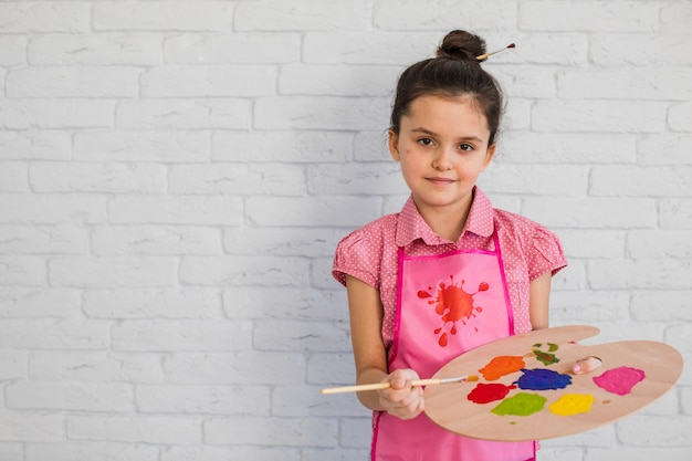 Ritratto di una bambina che tiene tavolozza multicolore e spazzola che sta contro la parete bianca