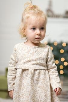Ritratto di una bambina con i capelli biondi in una foto di un albero di natale e decorazioni di capodanno alla vigilia di natale
