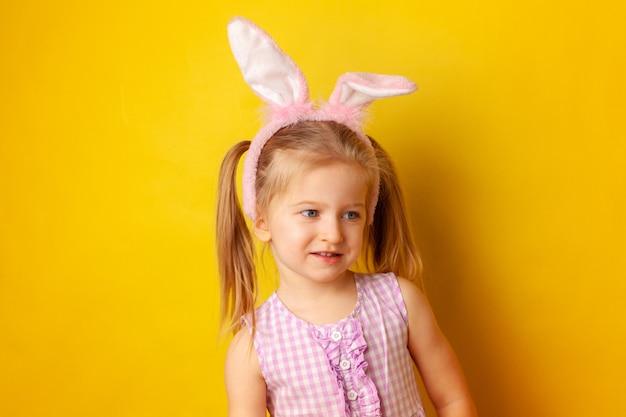 Ritratto di una bambina con le orecchie del coniglietto su giallo
