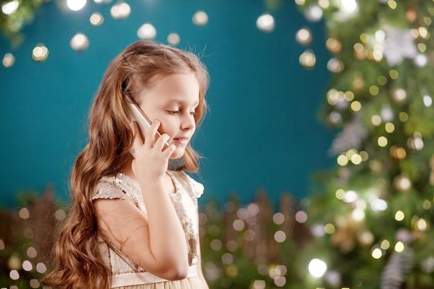 Ritratto di una bambina dai capelli lunghi sorridente in abito su luci di natale. bambina che parla al telefono. capodanno e natale.
