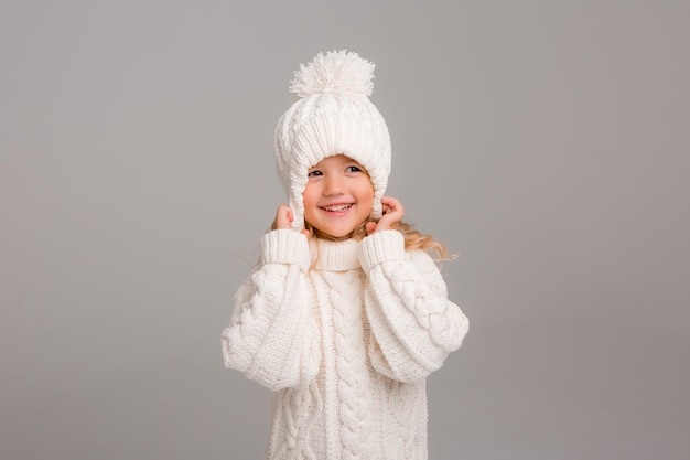 Ritratto di una bambina dai capelli ricci in un cappello bianco a maglia invernale
