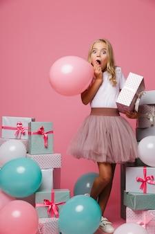 Ritratto di una bambina eccitata in un cappello di compleanno