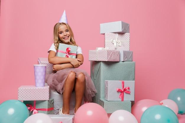 Ritratto di una bambina felice in un cappello di compleanno