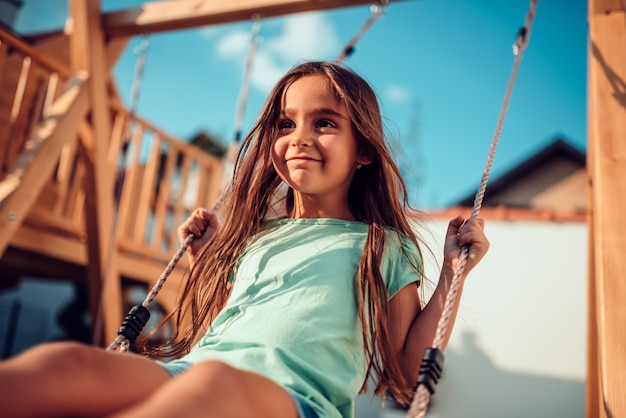 Ritratto di una bambina felice, seduto su un'altalena