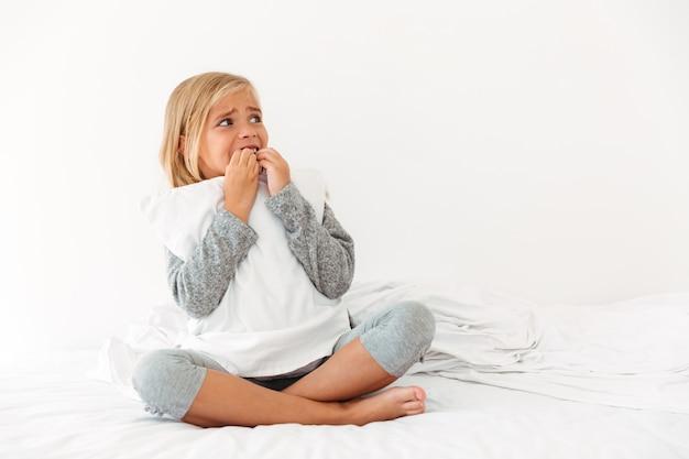 Ritratto di una bambina in preda al panico che abbraccia cuscino