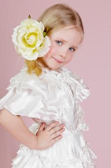 Ritratto di una bambina in un abito con fiore