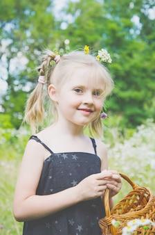 Ritratto di una bambina in un prato estivo con decorazioni di fiori di campo