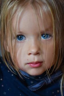 Ritratto di una bambina romantica triste con grandi occhi blu dall'europa orientale, primo piano, sfondo scuro