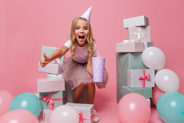 Ritratto di una bambina sorpresa in un cappello di compleanno