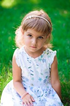Ritratto di una bambina sorridente che si siede sull'erba verde.