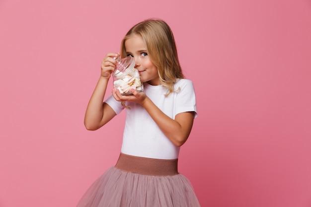 Ritratto di una bambina sorridente marshmallow sentente l'odore