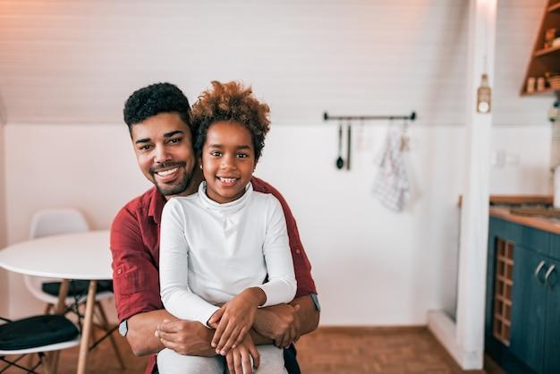 Ritratto di una bambina trascorrere del tempo con suo padre a casa, abbracciando e guardando la fotocamera.